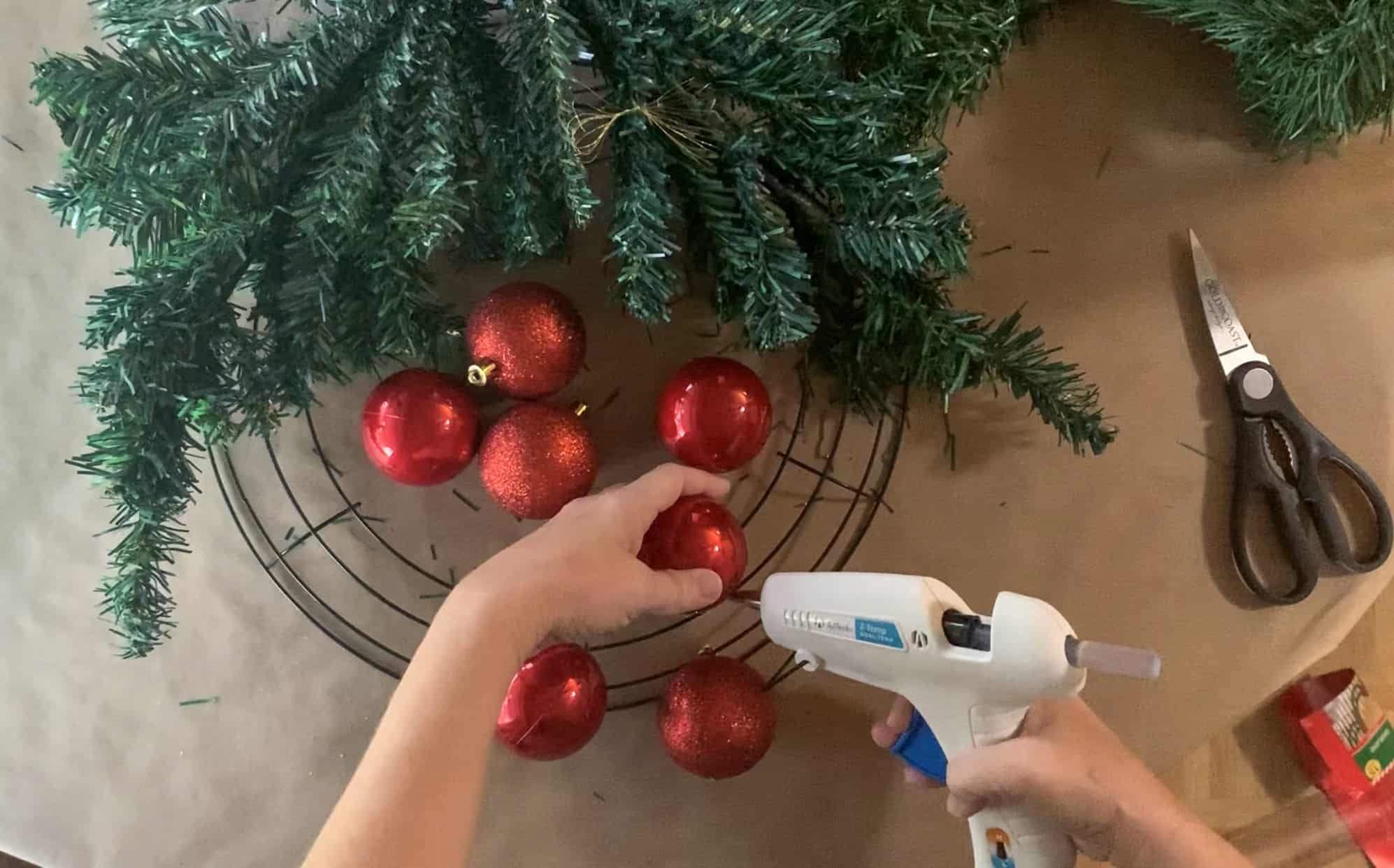 Using hot glue to secure the larger ornaments to the wire wreath form.