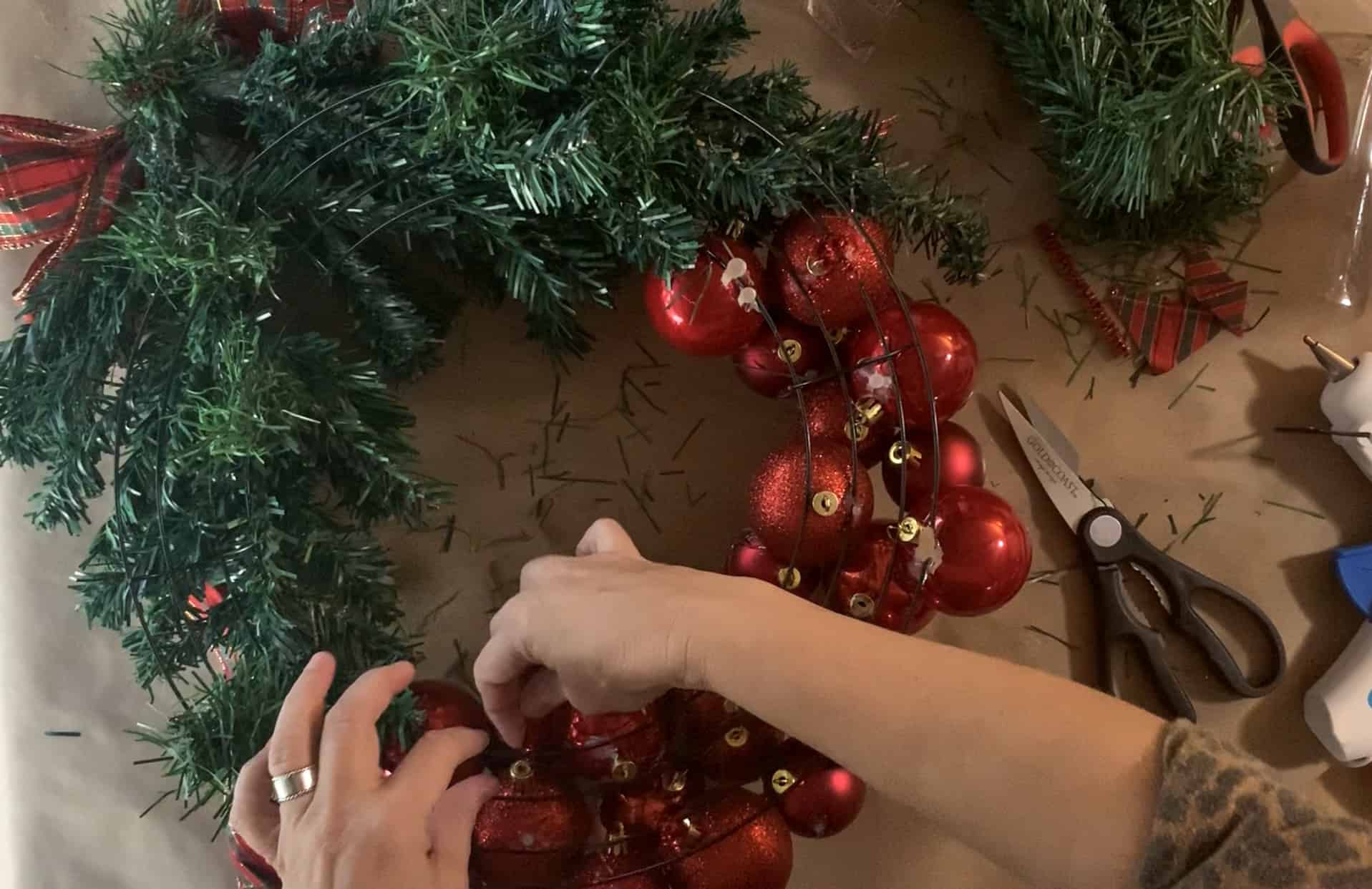 Using pipe cleaners to firmly secure ornaments to wire wreath form.