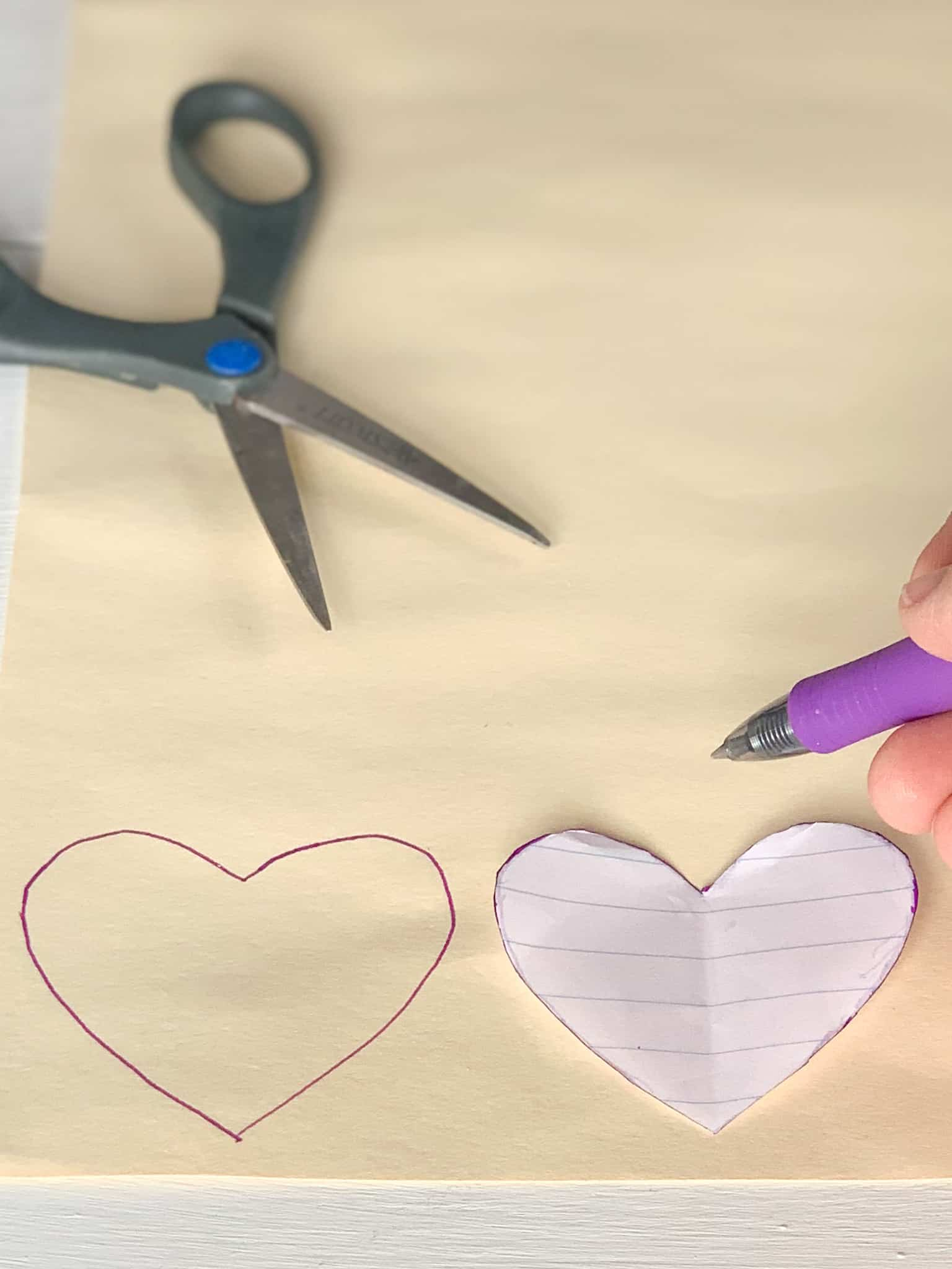 Tracing hearts onto file folder.