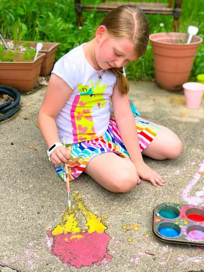 Young girl painting with diy magic sidewalk chalk.