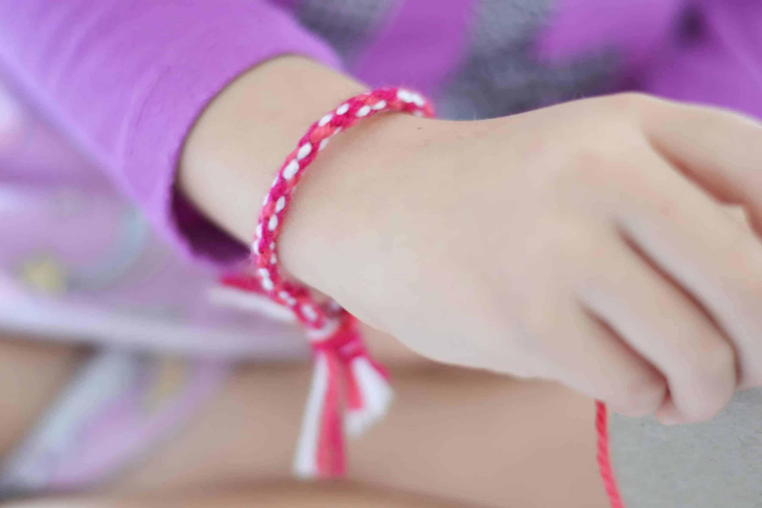 DIY friendship bracelet on young girl's wrist.