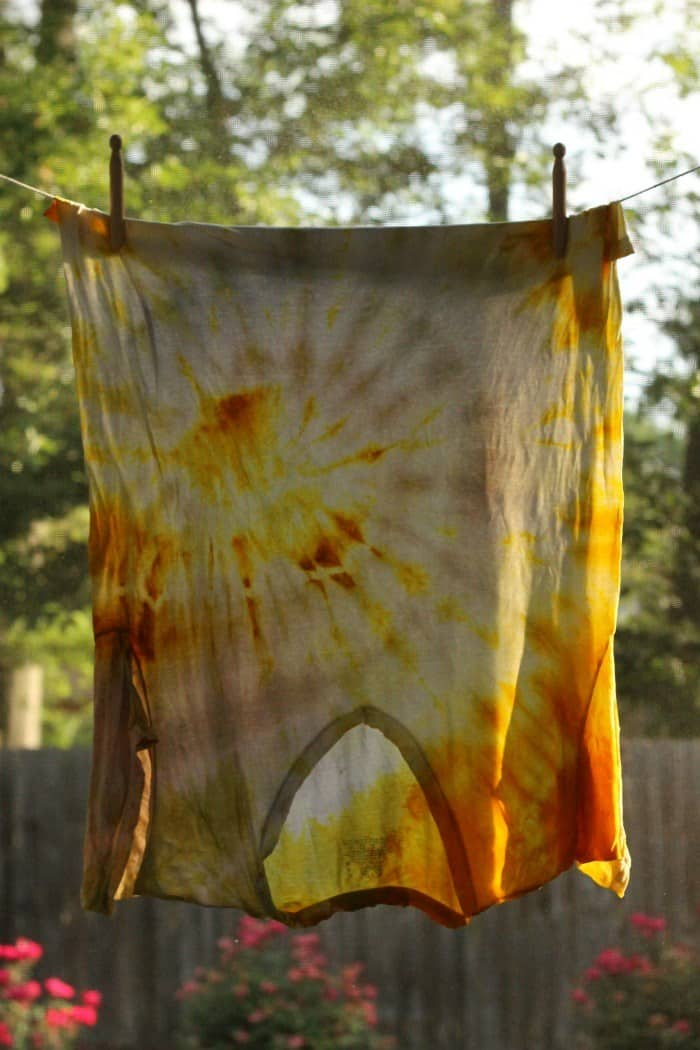 Turmeric tie dyed t-shirt hanging upside down from a clothesline outdoors.