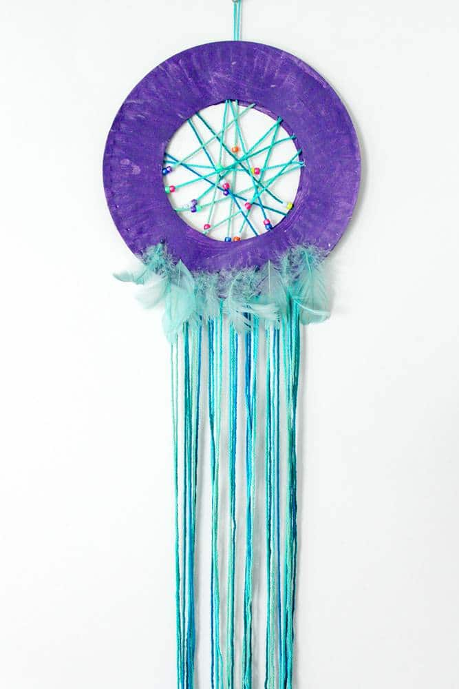 Paper plate dream catcher with beads and feathers craft project.