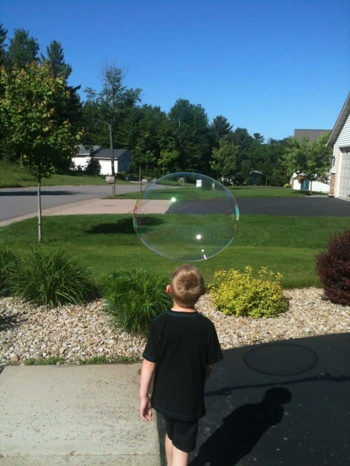Young boy in yard with gigantic bubble floating by him.