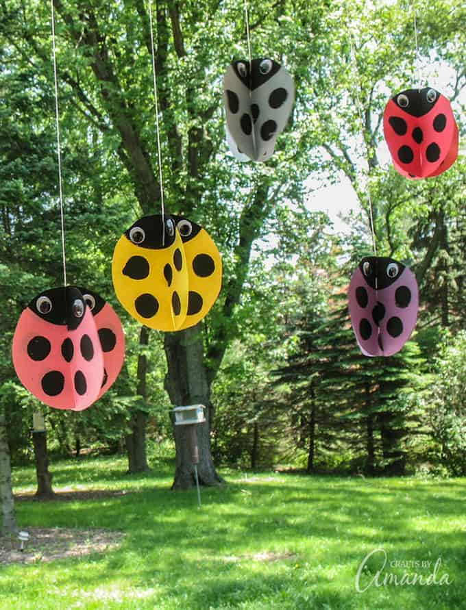 Twirling ladybug crafts hanging from a tree.