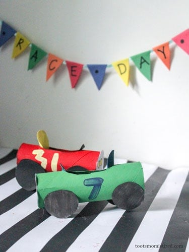 A red and a green toilet paper roll race cars.